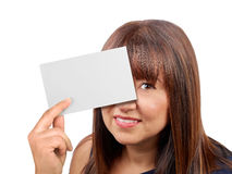 Brunette woman holding hiding behind blank card isolated. Brunette woman holding and hiding behind blank card isolated Royalty Free Stock Images