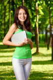 Brunette woman holding laptop. Woman standing in summer park and holding netbook royalty free stock photo