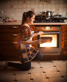 Brunette woman holding pan with cookies near oven Stock Photo