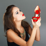 Brunette woman holding red high heels Royalty Free Stock Image