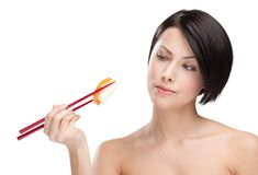Brunette woman holding sushi with a chopsticks Stock Images