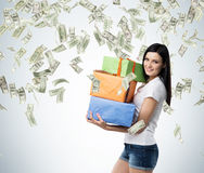 A brunette woman is holding three colourful gift boxes. Royalty Free Stock Images