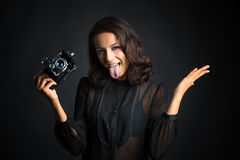 Brunette woman holding  vintage camera with open tongue Royalty Free Stock Photography