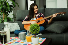 Brunette woman at home playing the guitar Stock Images