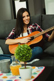 Brunette woman at home playing the guitar Royalty Free Stock Image