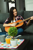 Brunette woman at home playing the guitar Stock Photography