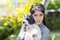 Brunette woman hugging  her white  dog outdoor Stock Photos