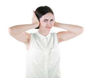 A brunette woman isolated over the white background. A disgusted girl closing her ears. A disappointed young woman. royalty free stock photography