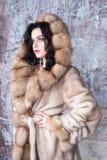 Brunette woman with jewelry wearing luxury fur coat. Fashion model girl portrait, studio shot. Winter clothes. Brunette woman with jewelry wearing luxury fur Royalty Free Stock Image