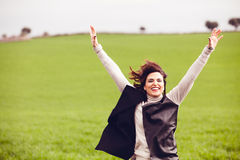 Brunette woman jumping in the countryside. Royalty Free Stock Photo