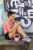 Brunette woman with kettlebell and smartphone Royalty Free Stock Photo