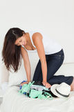 Brunette woman kneeing on suitcase Royalty Free Stock Photos