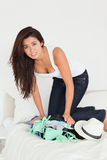 Brunette woman kneeing on suitcase trying to close Stock Image