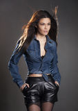 Brunette woman in leather pants and jean jacket Stock Photography