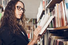 Brunette woman at library. Woman wearing glasses reading book at library Stock Photo