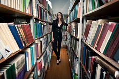 Brunette woman at library stock images