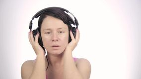 Brunette woman listening music with big headphones and dancing on a light background stock video footage