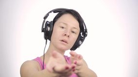 Brunette woman listening music with big headphones and dancing on a light background stock footage