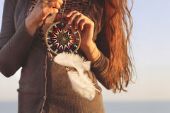 Brunette woman with long hair holding dream catcher. In her hands Stock Images