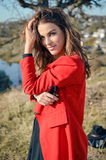 Brunette woman with long hair in red coat in Royalty Free Stock Images