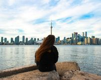 Girl sitting on a rock with a perfect view of the toronto skyline royalty free stock photos