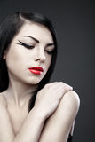 Brunette woman with long straight hair on dark Stock Image