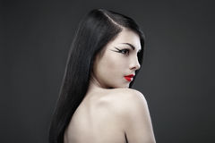 Brunette woman with long straight hair on dark. Pretty brunette woman with long straight hair on dark background Royalty Free Stock Image