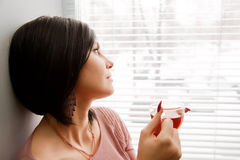 Brunette woman look at window Stock Photos