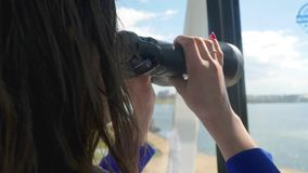 Brunette woman is looking through binoculars while rides on a ferris wheel. 3840x2160 stock footage