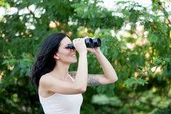 Brunette woman looking through the binoculars while strolling th. Rough a lush forest Royalty Free Stock Photos