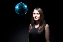 Brunette woman looking at disco ball Stock Images