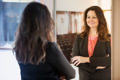 Brunette woman looking at herself in mirror. Beautiful brunette woman looking at herself in mirror Royalty Free Stock Photo