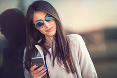 Brunette woman looking at mobile phone outdoor Royalty Free Stock Photo