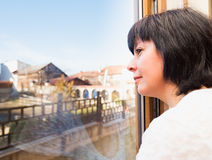 Brunette woman looking out the window Royalty Free Stock Images