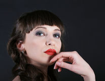 Brunette woman looking seriouse. Brunette woman looking dreamling and looking to the camera over dark background Royalty Free Stock Images