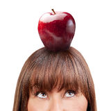 Brunette woman looking up apple isolated Stock Photography