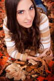 Brunette woman lying on autumn leaves Royalty Free Stock Photography