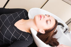 Brunette Woman Lying Back with Head in Salon Sink Royalty Free Stock Photography