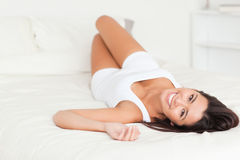 Brunette woman lying on bed Stock Photos