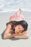 Brunette woman lying down on beach Stock Image