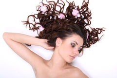 Brunette woman lying with flowers Stock Photo