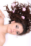 Brunette woman lying with flowers Stock Photography