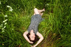 Brunette woman lying on green grass royalty free stock image