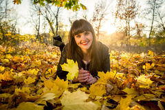 Brunette woman lying on ground covered with leaves at autumn par Stock Photography
