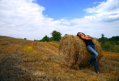 Brunette woman lying in haystack. Background nature and sky royalty free stock photos