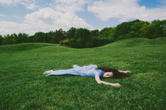 Brunette woman lying on her stomach on the green grass Stock Photo