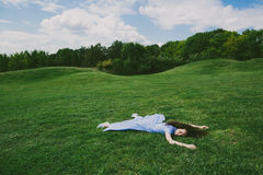 Brunette woman lying on her stomach on the green grass Stock Photography