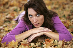 Brunette woman lying in leaves Stock Image