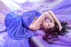 Brunette woman lying in long purple dress lying Stock Photo