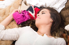 Brunette woman lying on pile of clothes smiling posing naturally, shopping fashion concept Stock Image